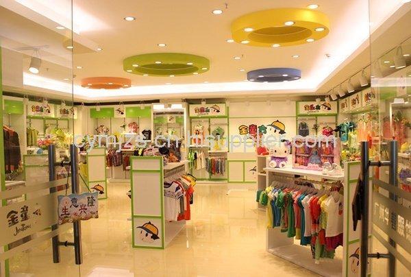 實木地板暖和舒適的質感給小朋友舒適的選衣環境,低矮的展示書桌與孩子的視角相適應,他們可以與展示的衣服和玩具形成互動,增加他們的喜好度。店鋪的裝修風格現代簡約,主題色是以頂棚的淺藍綠色和暖黃色,吊頂的射燈像一顆顆星星,吸引孩子觀望。店內的展示服裝是以明亮的黃紅色為主,顯得極為突出。